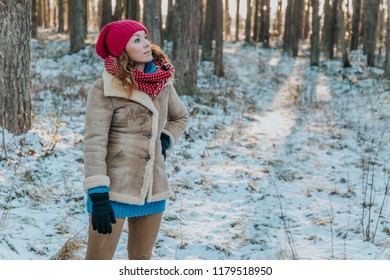 Blonde beautiful girl looking up inside winter forest with snow, with sunset light, inside the woods wearing warm clothes