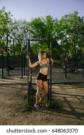 Blonde beautiful girl training in a public open air gym