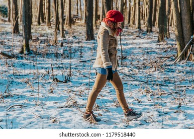 Blonde beautiful girl walking inside snowy winter forest, wearing warm winter clothes and being active