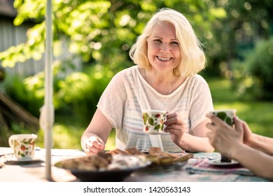 Blonde beautiful grandmother relaxing with her family at the garden