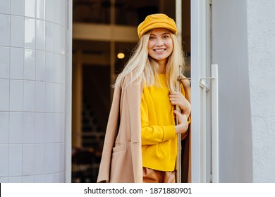 Blonde beautiful positive woman holding open door, standing at entrance or doorway, outdoor portrait. Young trendy female in yellow hat and sweater,wearing beige coat looking at camera. Street fashio