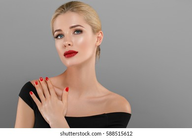 Blonde beautiful woman model over gray background. Woman nail manicure lipstick same color beauty portrait beautiful care