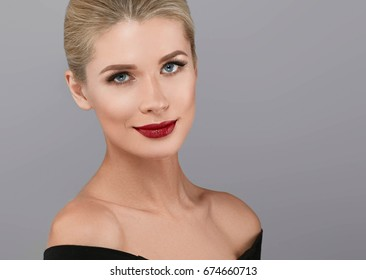 Blonde beautiful woman model over gray background. Red lipstick lips model face portrait.