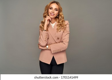 Blonde beautiful woman in smart business attire isolated on gray background