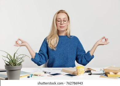Blonde beautiful young female has relaxation after long tiredsome work with papers and books, meditates at working place, tries to concentrate, has minute rest, isolated over white background.