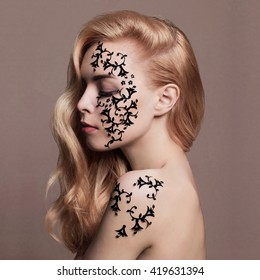 blonde beauty girl with body-art mask on her face and body.unusual make-up Young beautiful woman