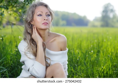 Blonde beauty sitting in green field