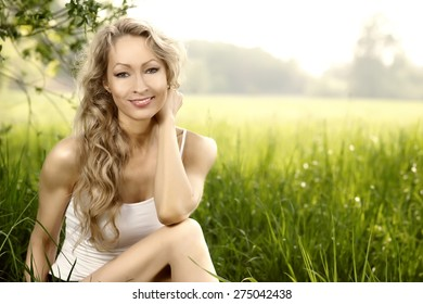 Blonde beauty sitting in green field golden look