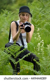 blonde with black hat photographed in nature