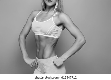 Blonde bodybuilder young adult sexy girl with long hair. Portrait of slim sporty. VERY HOT woman. Copy space. Flat stomach with press.