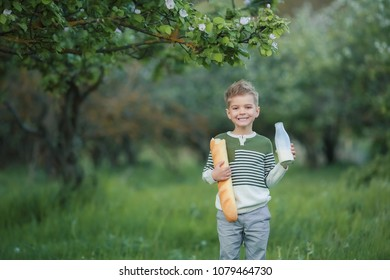 Blonde boy with milk and bread in a green garden