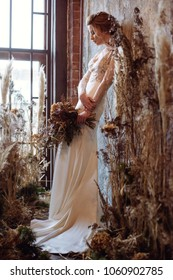 Blonde bride in fashion white wedding dress with makeup. Wedding day of bride in bridal gown. Beauty woman and bouquet. Fashion blonde model indoors. Beauty portrait of model in white bridal dress