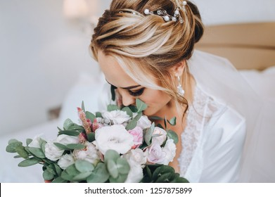 Blonde bride sits on a white bed and sniffs a bouquet. Wedding interior. Charges the bride at the hotel. Wedding photography. Portrait of a cute bride.
