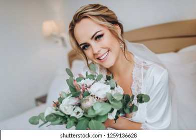 The blonde bride sits on a white bed with a bouquet and smiles sweetly. Wedding interior. Charges the bride at the hotel. Wedding photography. Portrait of a cute bride.