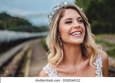 Blonde bride with tiara smiling and looking to the side