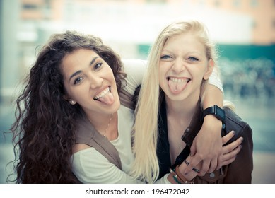 blonde and brunette beautiful stylish young women in the city