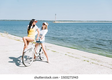 blonde and brunette girls with bike near river in summer