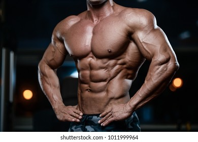 blonde brutal sexy strong bodybuilder athletic fitness man pumping up abs muscles workout bodybuilding concept background - muscular handsome men doing health care fitness exercises in gym naked torso
