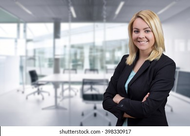 Blonde business woman with crossed hands looking in to camera on bright office background