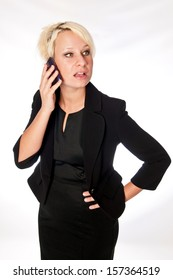 Blonde business woman on a mobile phone, looking camera right with a concerned look on her face.