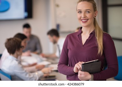 Blonde businesswoman in casual  clothes working on tablet computer at modern startup business office interior. Young people group on team meeting blured  in background