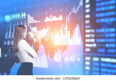 Blonde businesswoman looking at infographics and world map interface. Future of hi tech and globalisation concept. Toned image double exposure Elements of this image furnished by NASA