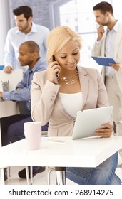 Blonde businesswoman with mobile and tablet pc in busy office.