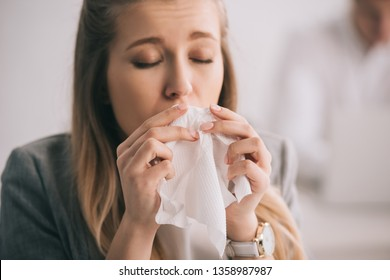 blonde businesswoman sneezing in tissue with closed eyes in office
