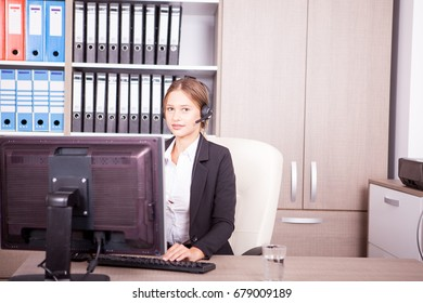 Blonde call center operator talking in the headset with the client