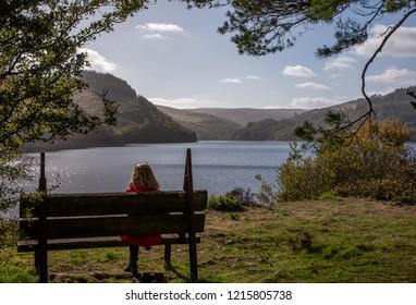 BLonde, Caucasian, female sat on an old bench overlooking Elan Valley Reservoir., Wales, UK