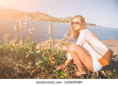 Blonde caucasian woman, aged 30-39, enjoying the beautiful scenic of french rivera with wild flower in the agay bay , light flare, holiday concept,