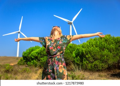 A blonde caucasian woman with open arms enjoying happiness and enthusiasm for modern day power technology of wind turbines. Alternative energy concept. Sagres, Algarve in Portugal.