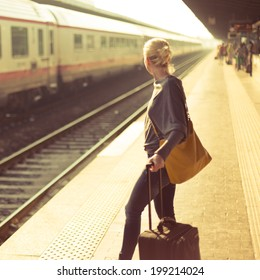 Blonde caucasian woman waiting at the railway station with a suitcase.