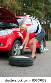 Blonde changing tire on a road