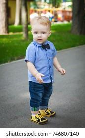 blonde child walking in the park in summer