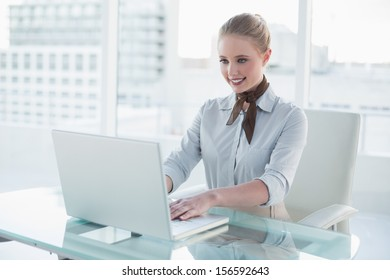 Blonde content businesswoman using laptop in bright office