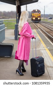 the blonde costs on the platform with a suitcase and waits for the train