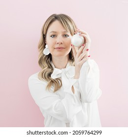 Blonde curly hair girl is holding white bauble in her hands. Red nails. New year minimal lady concept.