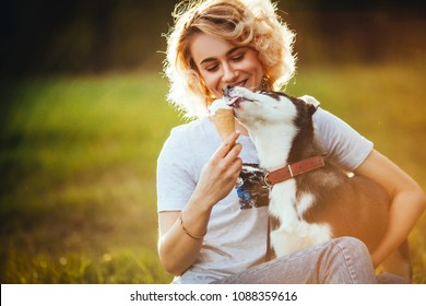 blonde with curly hair is smiling and is holding an ice cream in her hand that the pet licks in the park in the summer