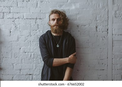 Blonde curly haired bearded man wearing hoodie and locket holding arm standing against white brickwall.