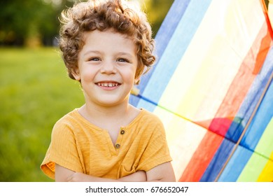 Blonde curly haired boy wearing yellow shirt holding arms folded on chest posing outside standing against kite.