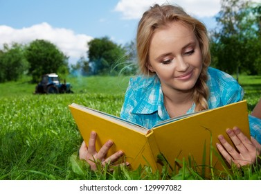 blonde cute girl laying on the grass and reading yellow book