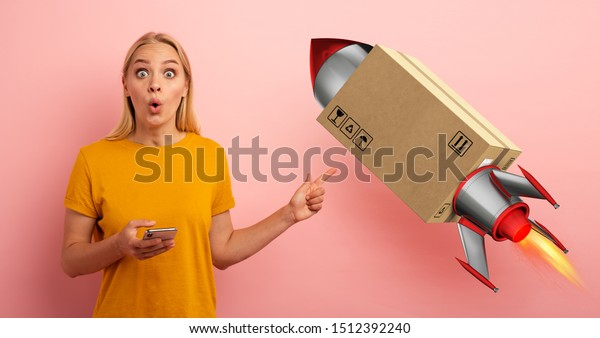 Blonde cute girl receives a priority fast box, like a rocket, from online shop order. Surprised and amazed expression. Pink background
