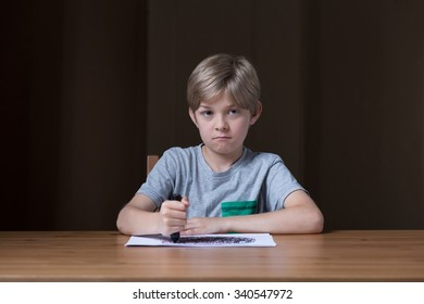 Blonde cute schoolchild drawing on the paper