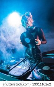 blonde dj woman looking at dj equipment and holding retro vinyl record in nightclub with smoke