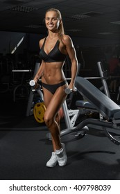blonde with dumbbells in gym