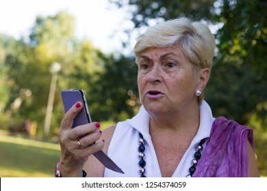 Blonde elder lady arguing over phone in the park. Senior woman having conversation through smarthphone speaker outdoors. Talk, discussion, problems, understanding concepts