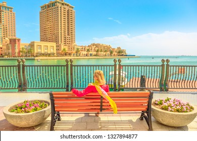 Blonde elegant woman sits at a bench in Porto Arabia, The Pearl-Qatar's main harbor. Caucasian tourist traveller in Doha, Persian Gulf, Middle East in Arabian Peninsula. Sunny day with blue sky.