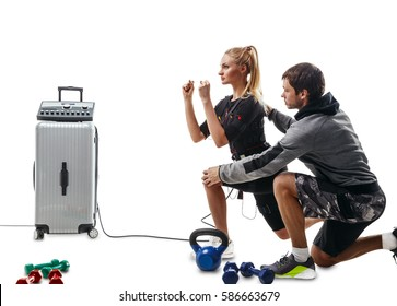 Blonde EMS fitness woman in full electrical muscular stimulation suit doing lunge exercise. Trainer helps her. Kettlebells and dumbbells around them. Isolated on white background.