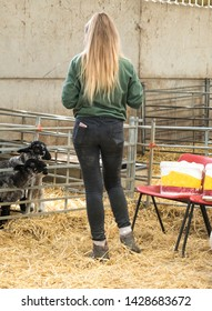 Blonde farm girl in dirty jeans seen from behind